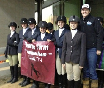 Row of youth equestrians preparing to walk into an arena with their coach