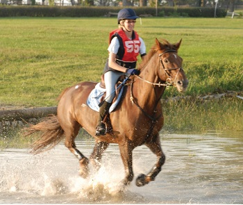 Pony Club youth member and horse galloping through cross-country water obstacle