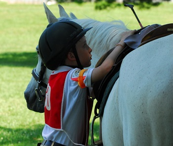 Youth member checking saddle before mounting horse
