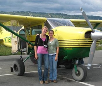 Visiting Instructors standing next to small sightseeing plane