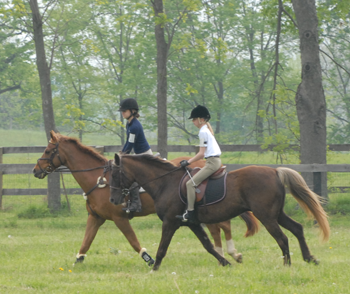 Two youth members riding their horses in the countryside