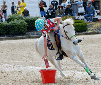 Youth member on pony leaning over to drop item into bucket during a games competition