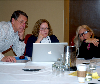 Committee Members at a table reviewing information on a laptop