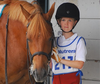 Youth member standing with her bridled horse