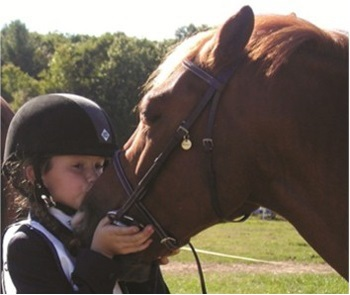 Child kissing her pony on the face