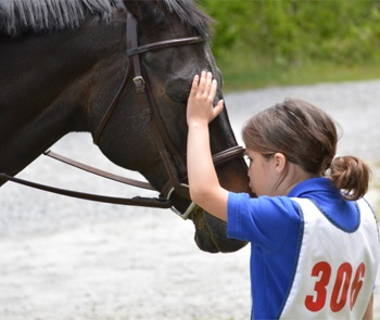 Child patting her horse and kissing it on the muzzle